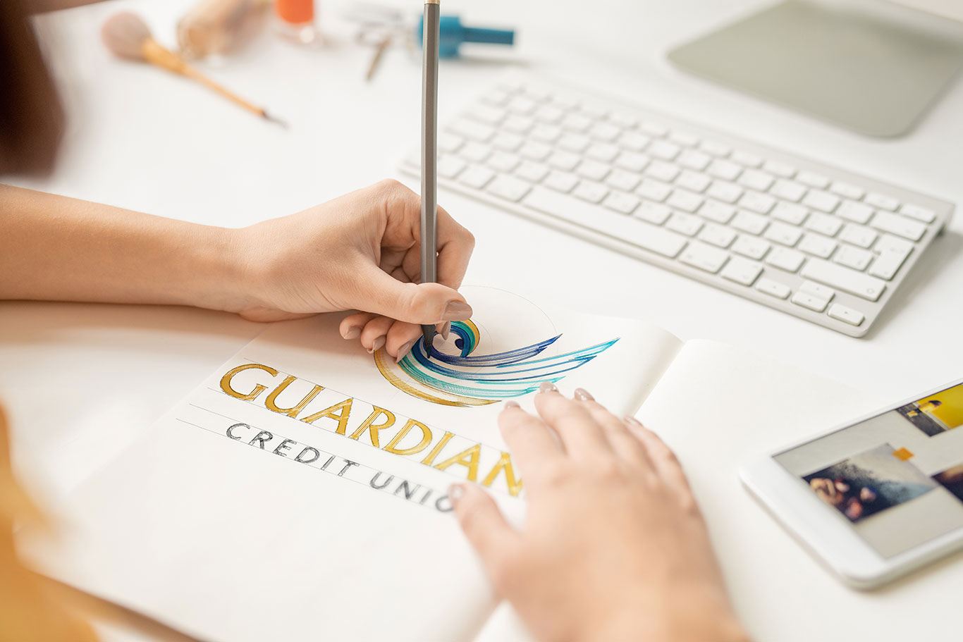 Hand illustrating the Guardians Credit Union logo on a piece of paper.