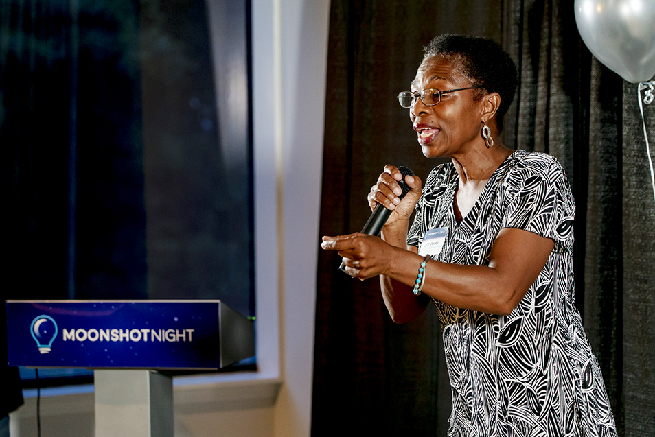 Woman giving speech on stage at a Moonshot Night event.