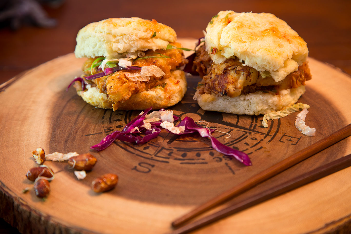 Two chicken biscuits on a wooden platter with a compass engraved on it.