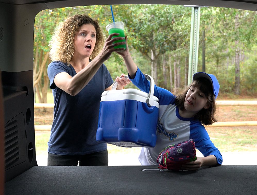Mother and daughter both grabbing for a green juice that is about to spill in the trunk of the car.