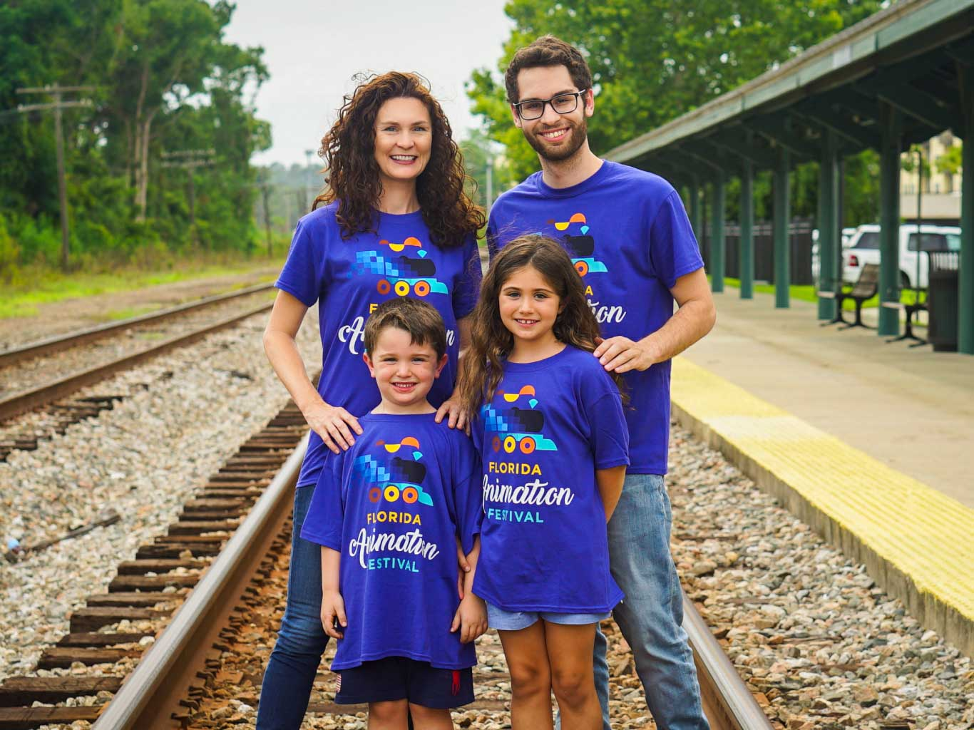 Young family standing on train tracks; wearing Florida Animation Festival t-shirts.