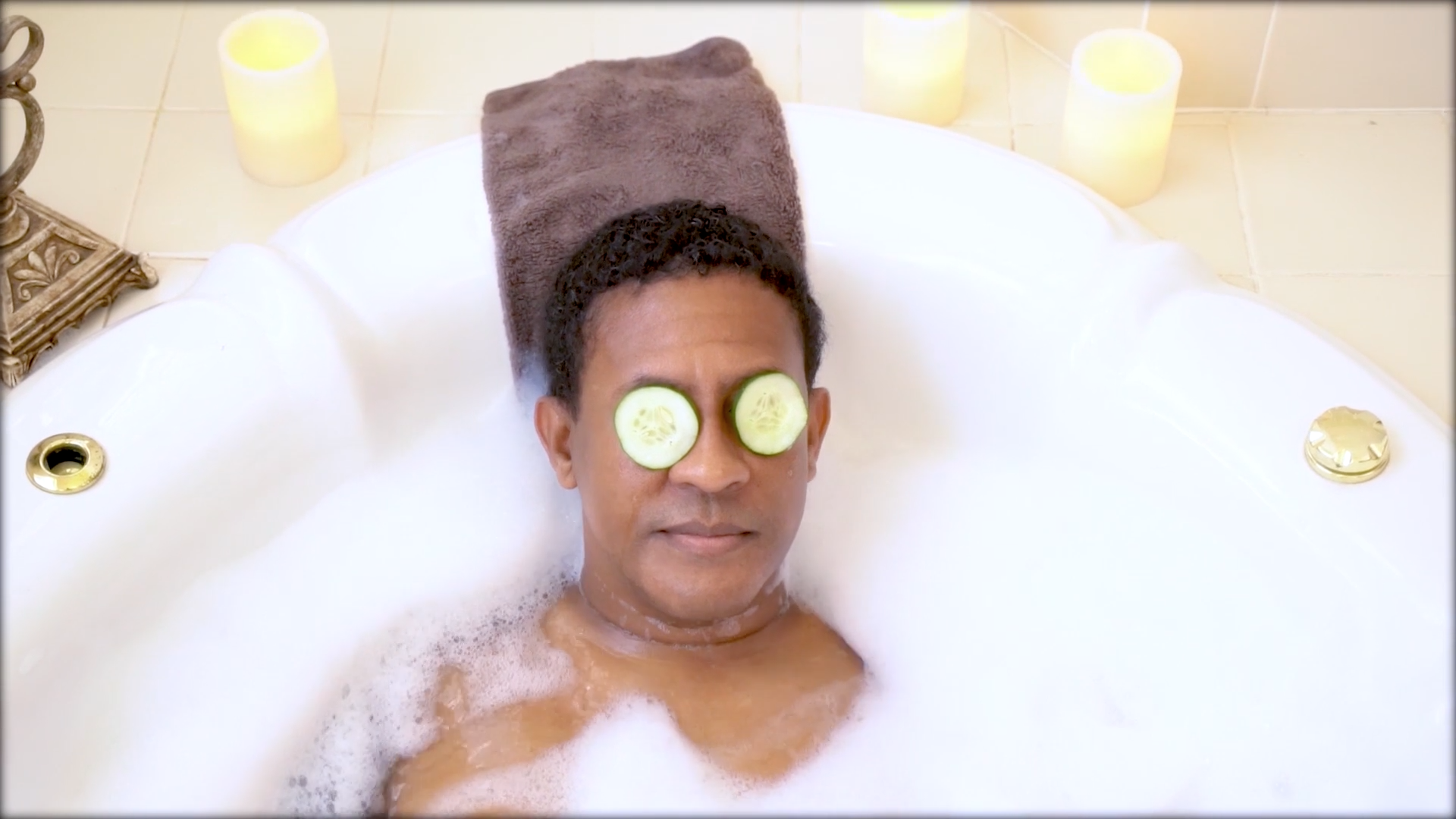 Man taking bubble bath with cucumbers on his eyes.