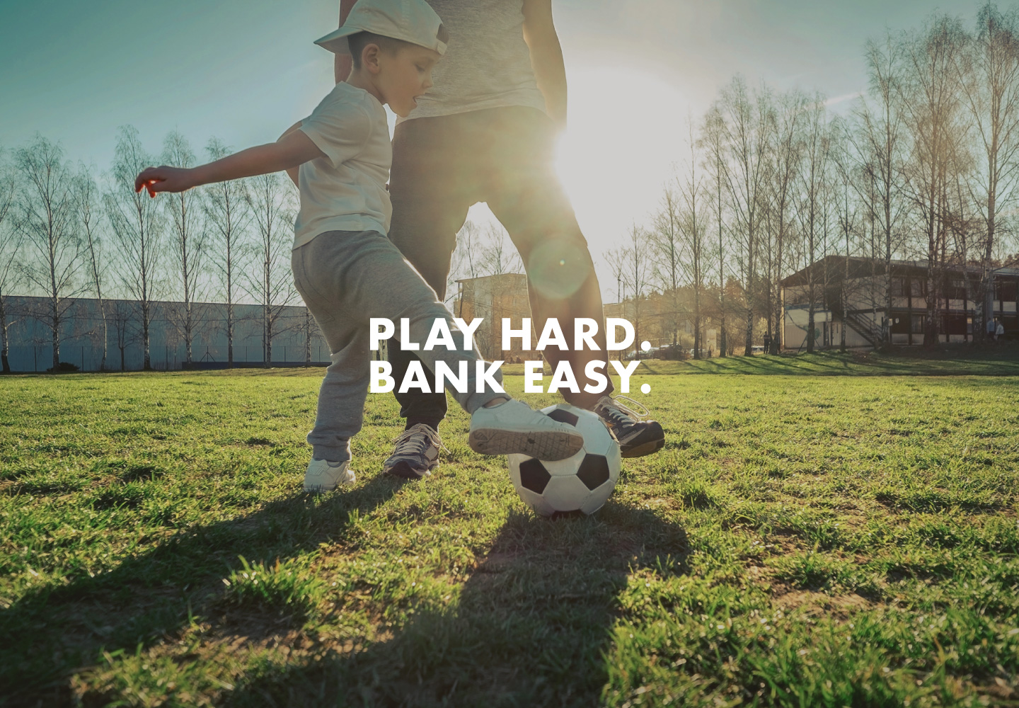 """Image of father and son playing in yard with words """"Play hard bank easy."""""""