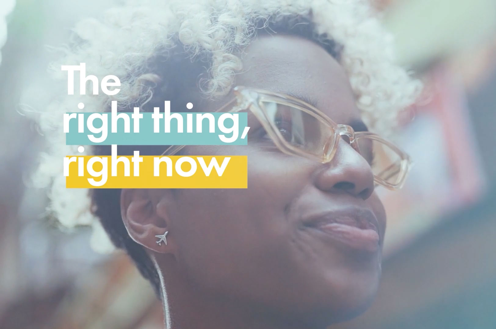 """Screenshot from commercial of African American woman with glasses looking off into distance with words """"The right thing, right now"""""""
