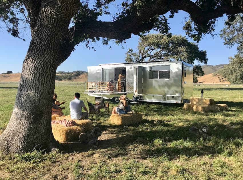 People hanging outside a luxury travel trailer