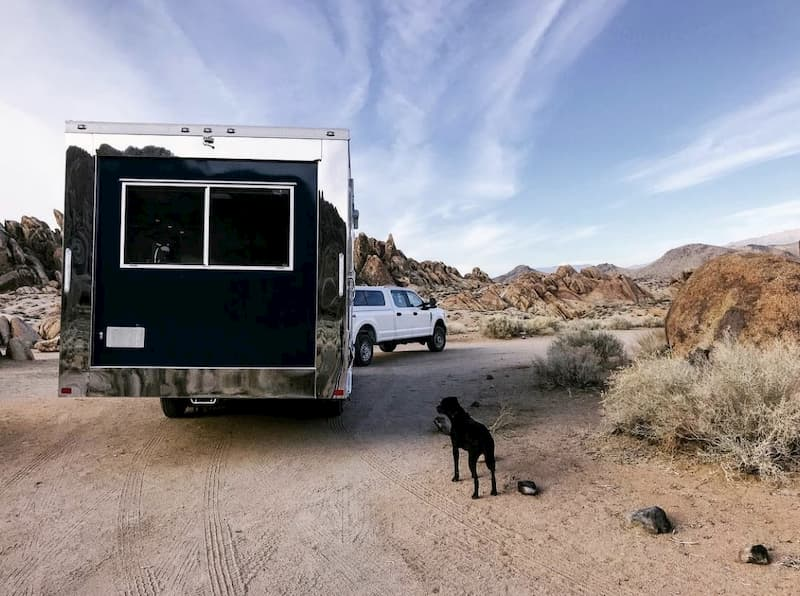 a dog in front of an off road travel trailer