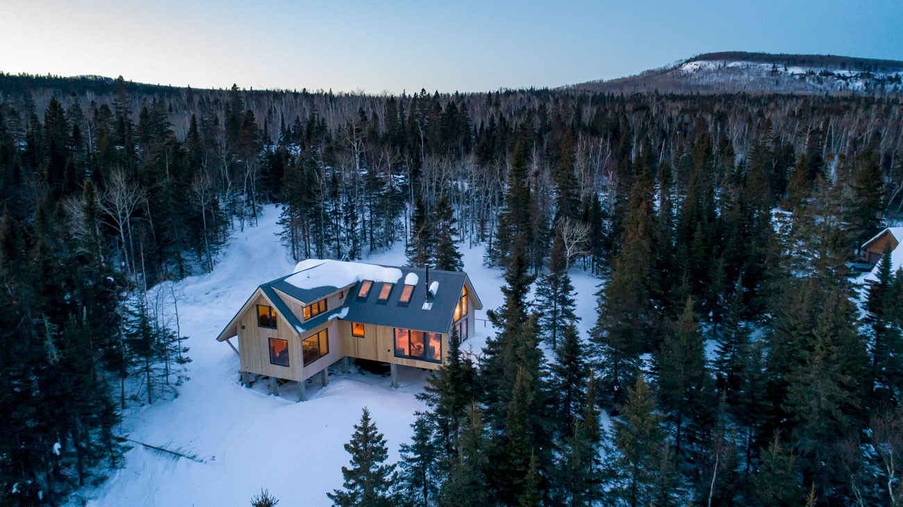 birds eye view of Snø Skur cabin on hillside at night
