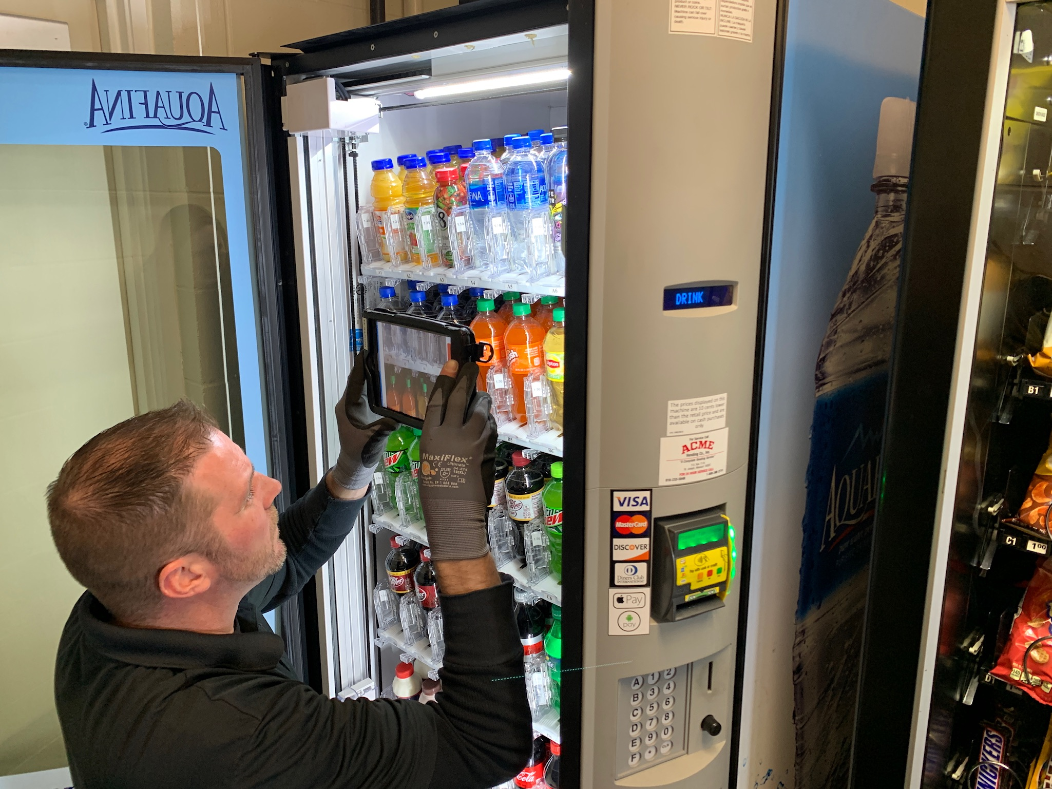 A route driver, Casey, from Acme Music & Vending using Gimme AutoDrive on a glassfront drink vending machine.