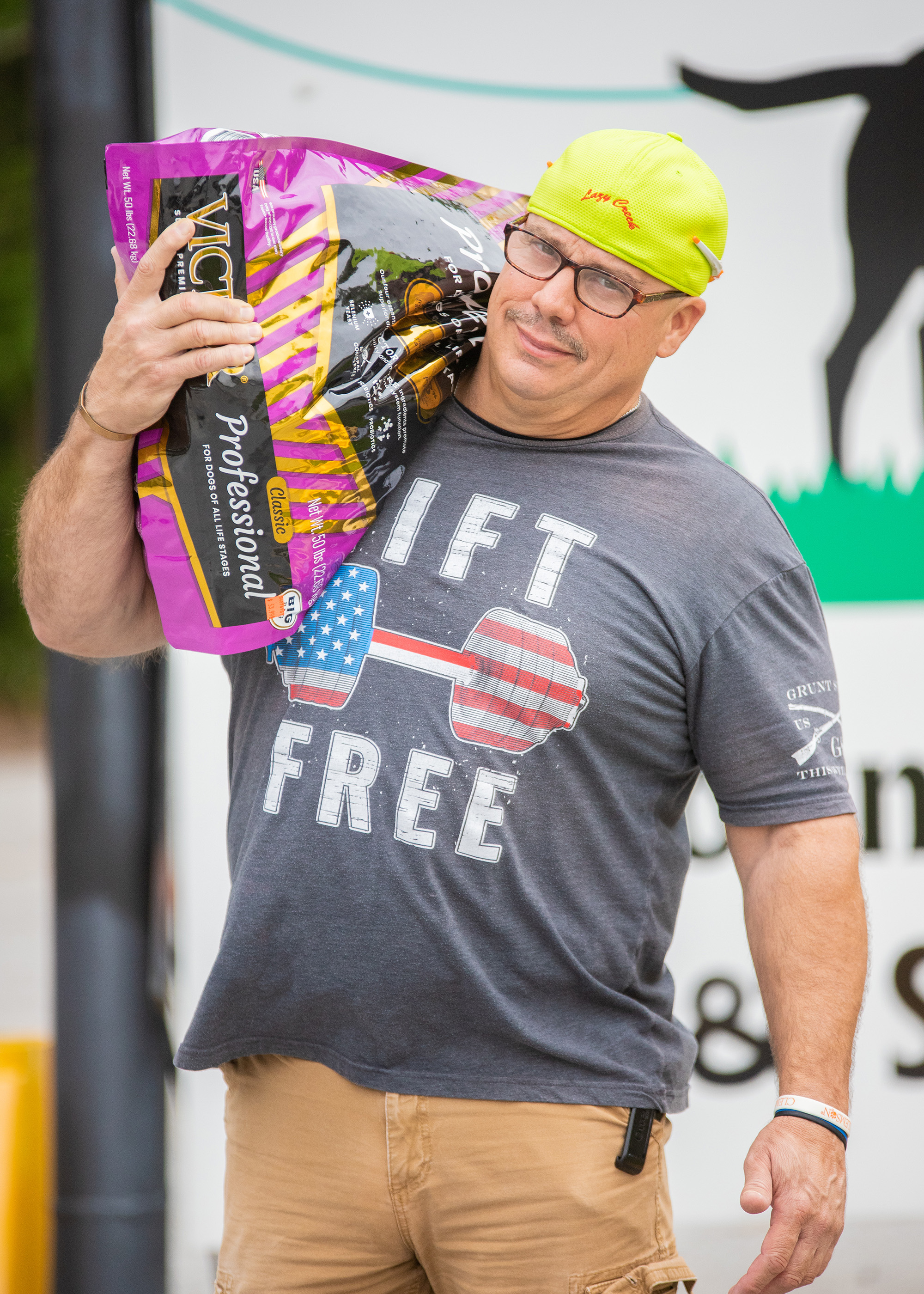 man carrying bag of dog food to customer car