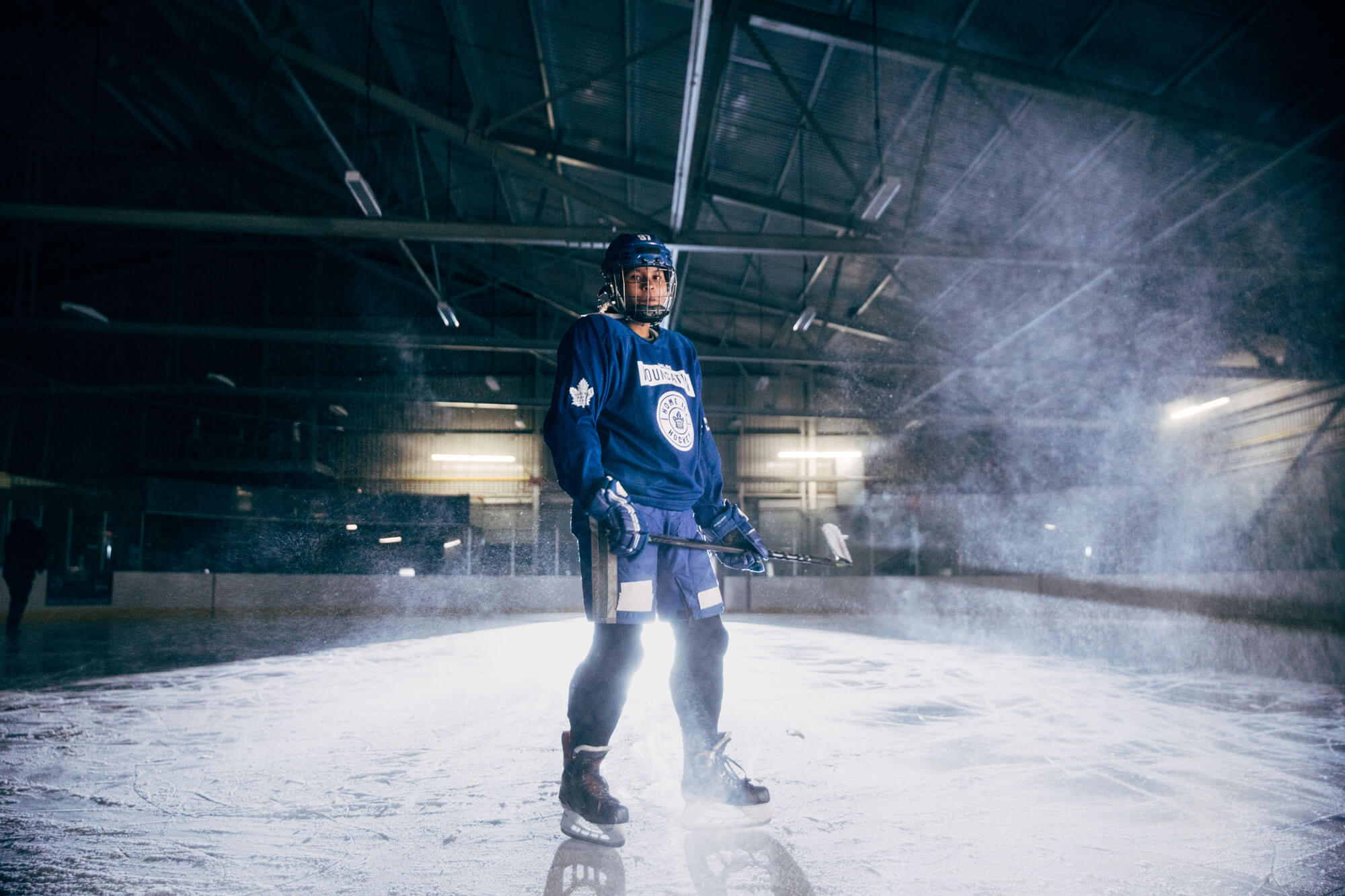 Female hockey player backlit by arena lights