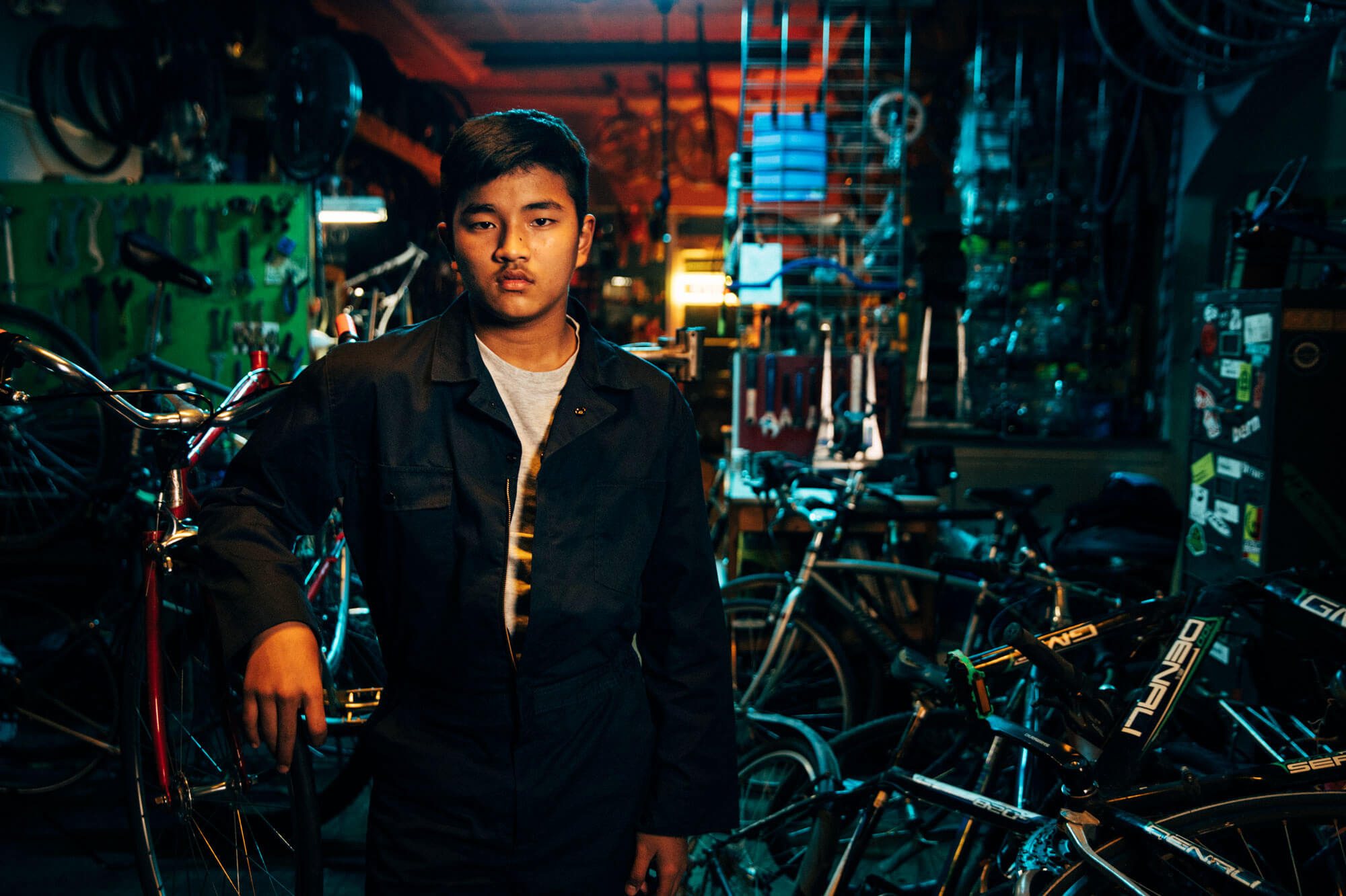 Young man poses at a bike shop in low-lighting