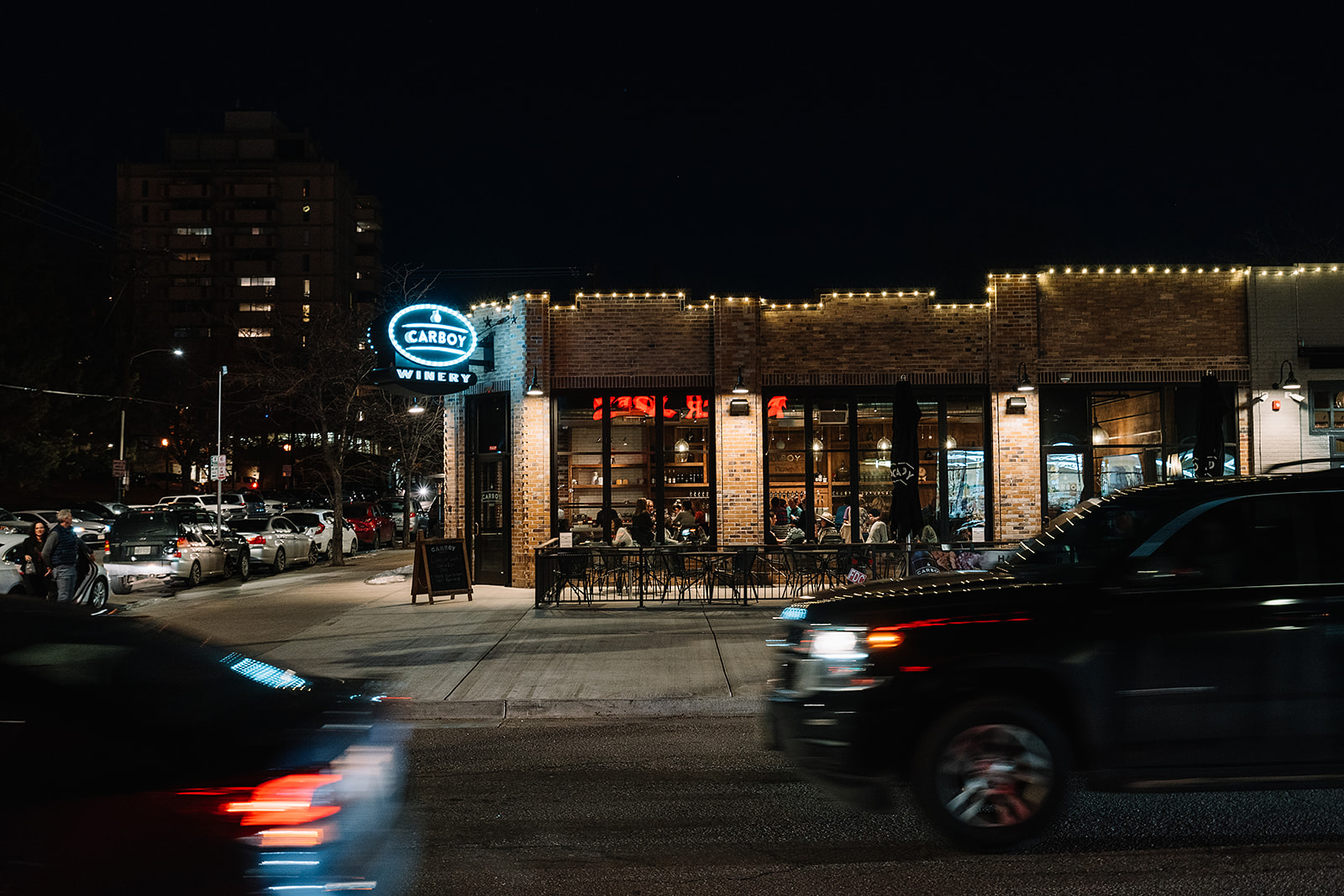Carboy Winery Denver exterior at night with cars driving by and the Carboy sign lit up.