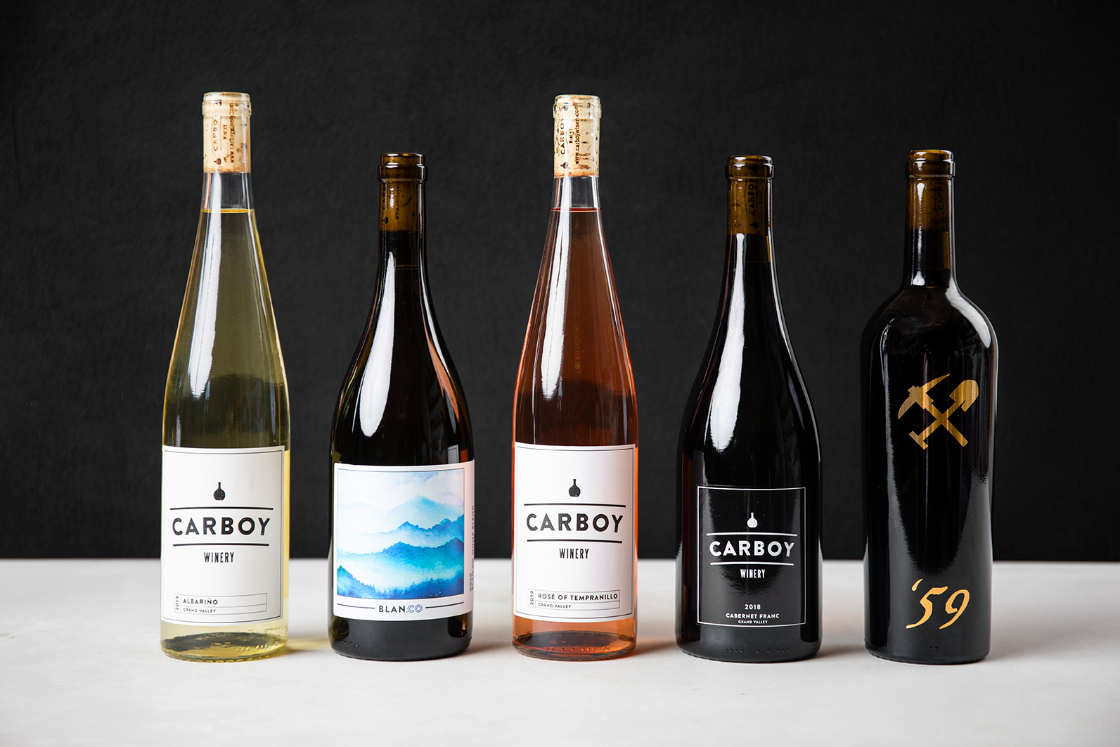 Five bottles of assorted Carboy Winery wines sit on a marble counter with a black background.