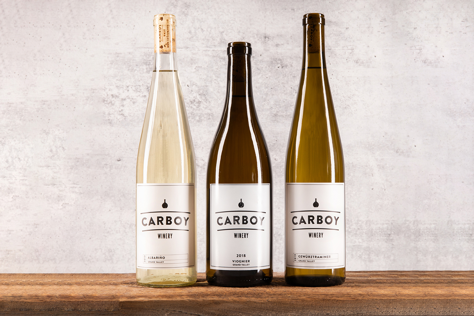 Three bottles of Carboy Winery wines sit on a wooden table with a concrete background.