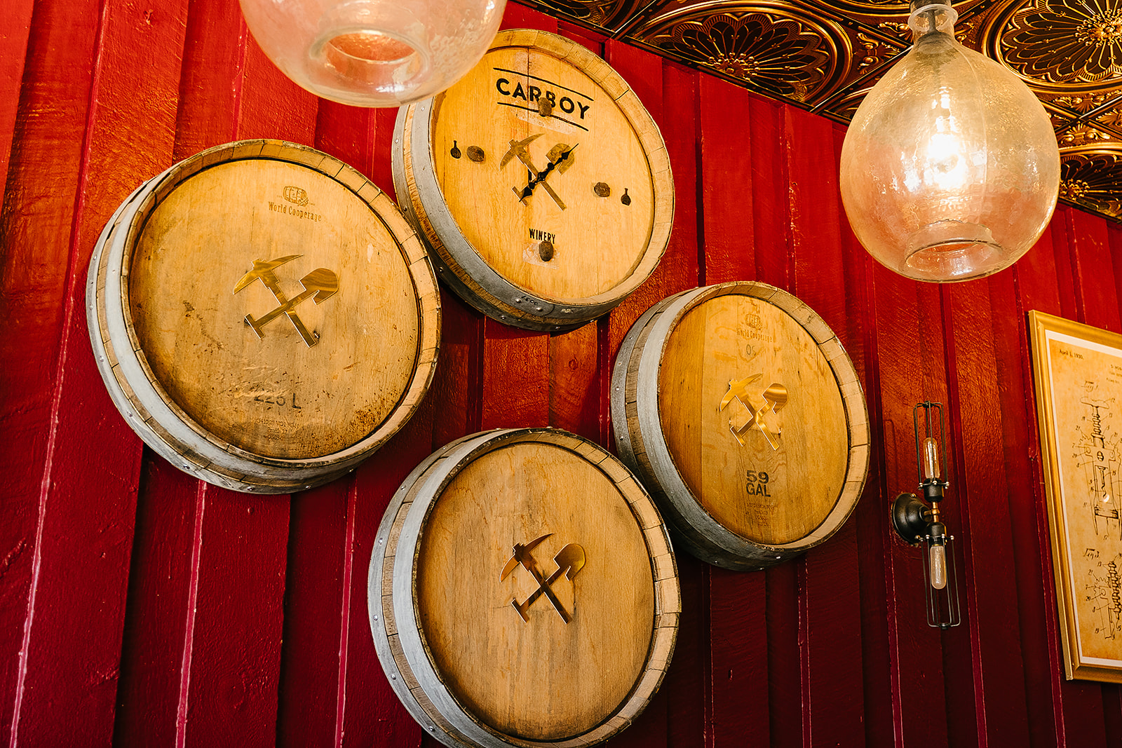 Carboy wine barrels stacked on a red wall.