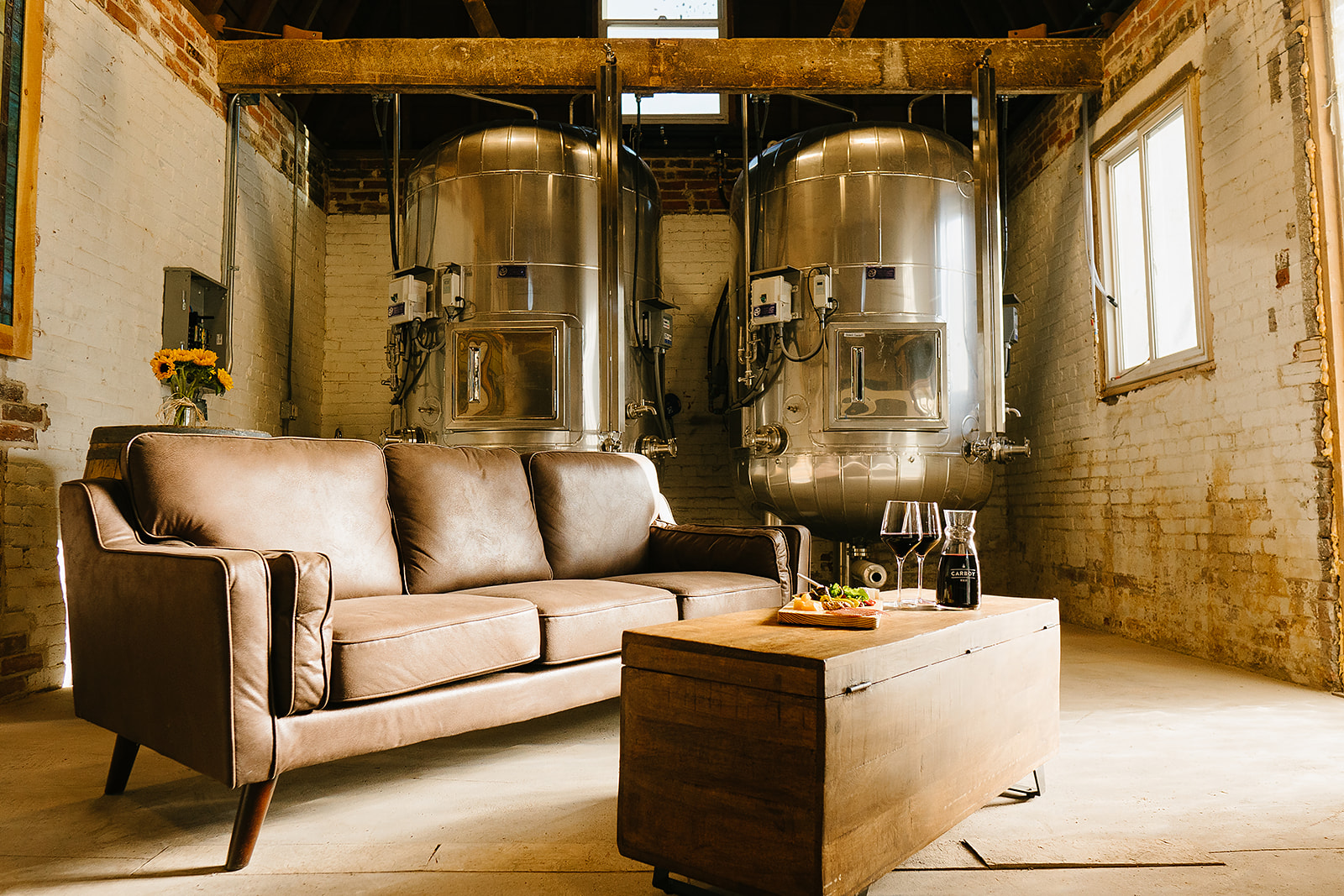 A couch sits in front of wine tanks in a private event room at Carboy Winery's Denver location.