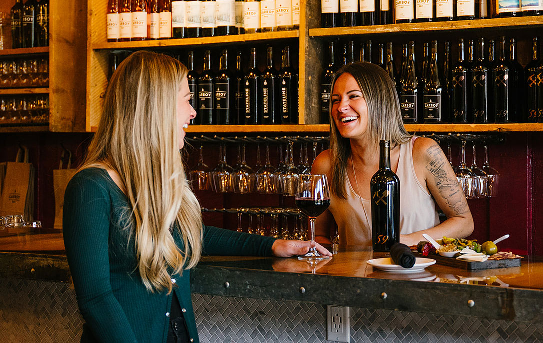 A wine specialist and customer talking at the bar.