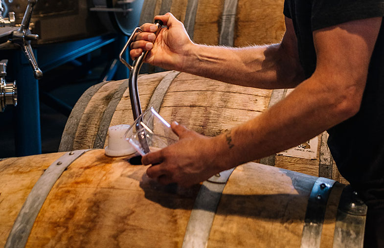 Carboy Winery winemaker samples wine from a wooden wine barrel.