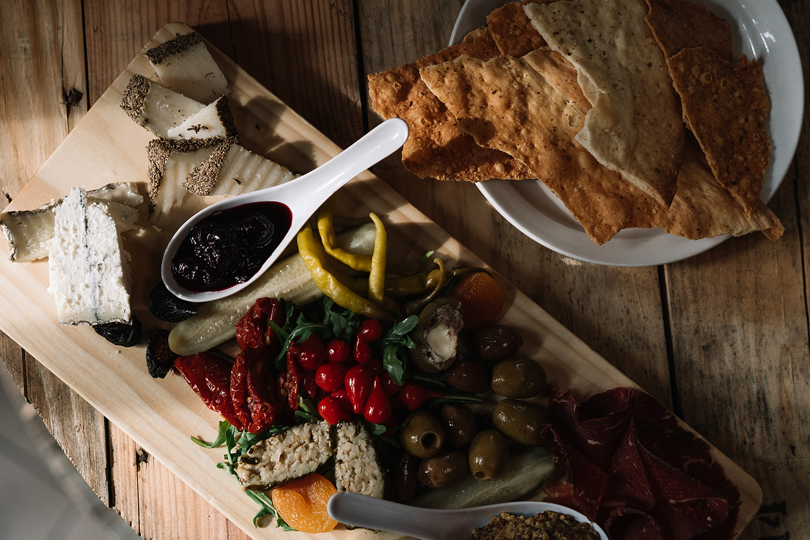 A charcuterie board full of meats, cheese and vegetables sits on a table with a plate of crackers.