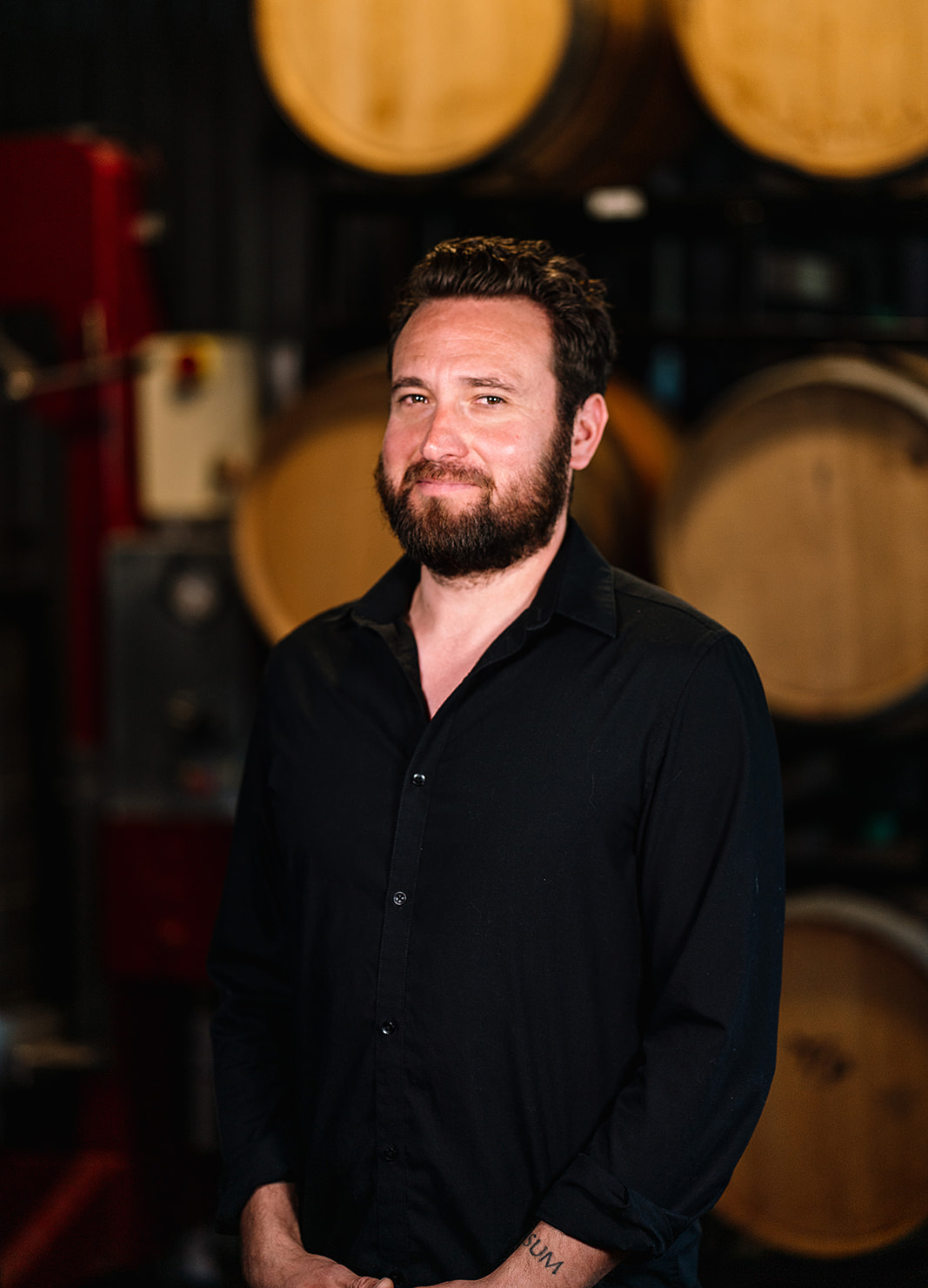 Carboy Head Winemaker, Tyzok Wharton, standing in front of wine barrels