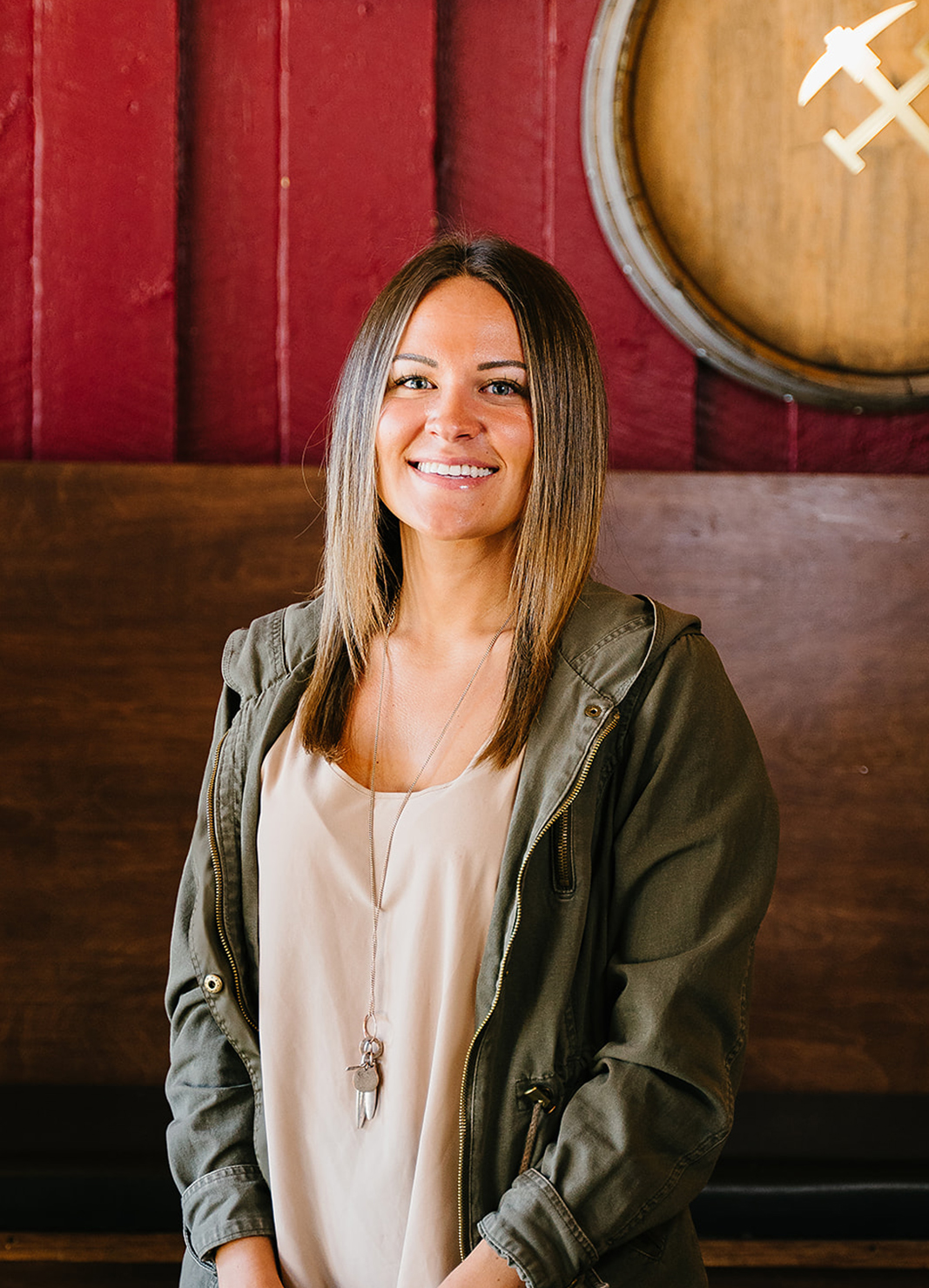 Carboy Tasting Room Manager, Kristen Kahl, standing in front of wine barrels