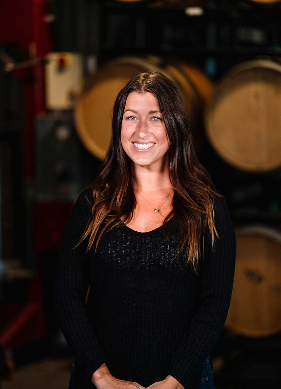 Carboy Events Coordinator, Mallory Eldred, standing in front of wine barrels