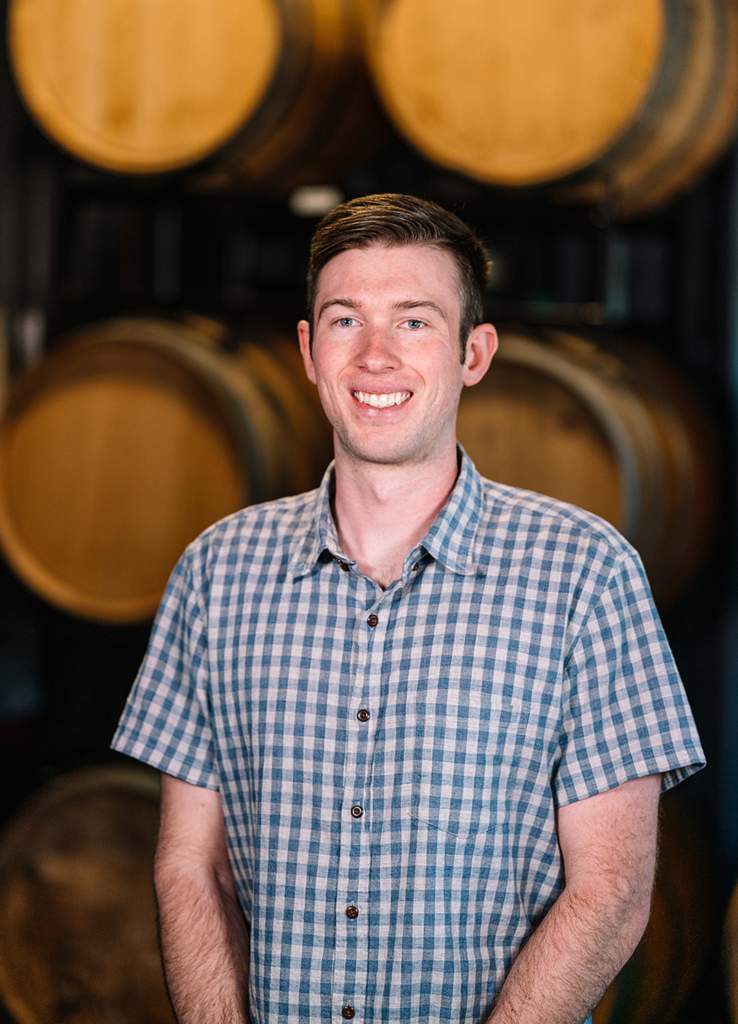 Carboy Production Specialist, Nic Carter, standing in front of wine barrels