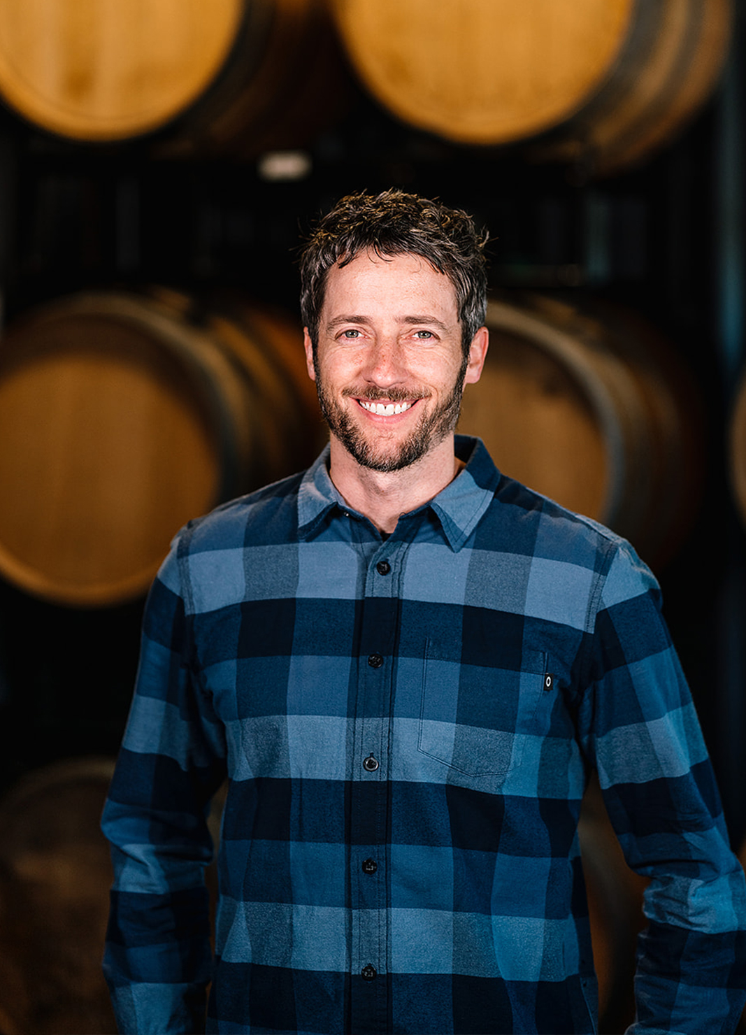 Carboy Sales & Market Strategy Director, Kevin Webber, standing in front of wine barrels