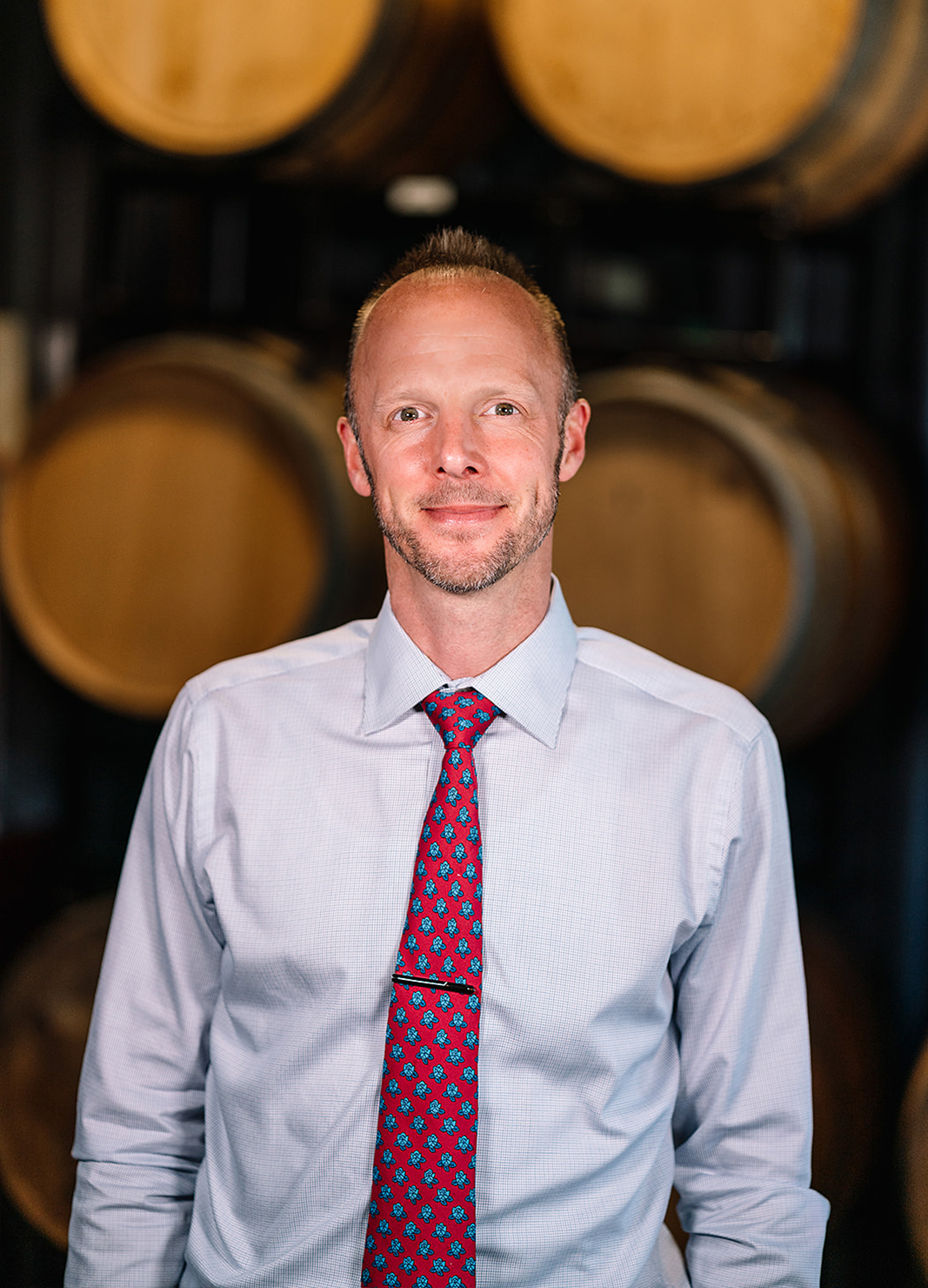 Carboy Wine Operations Director, Jason Snopkoski, standing in front of wine barrels