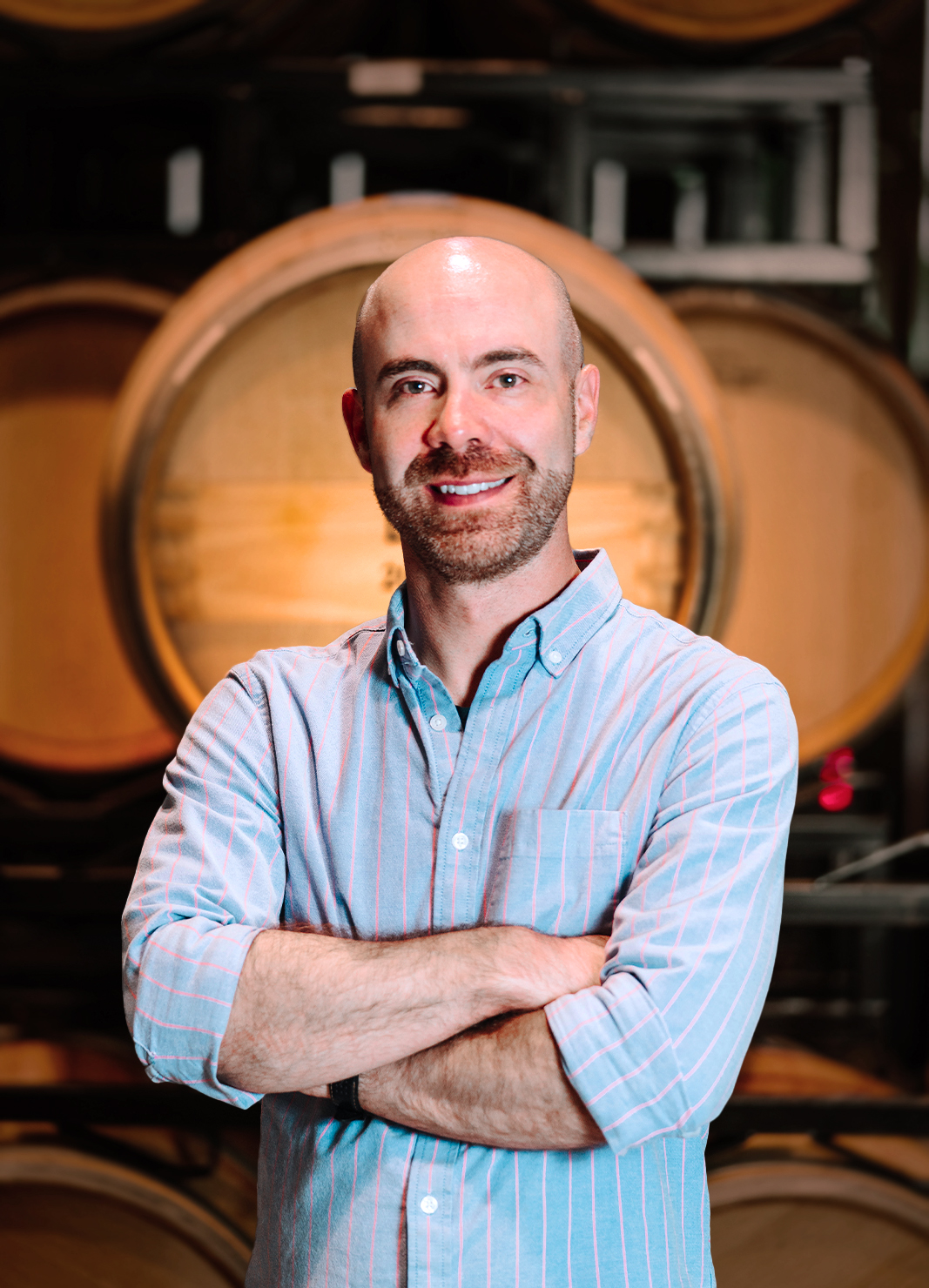 Carboy Wine Club Manager and Corporate Trainer, Kellen Brewer, standing in front of a wine barrel