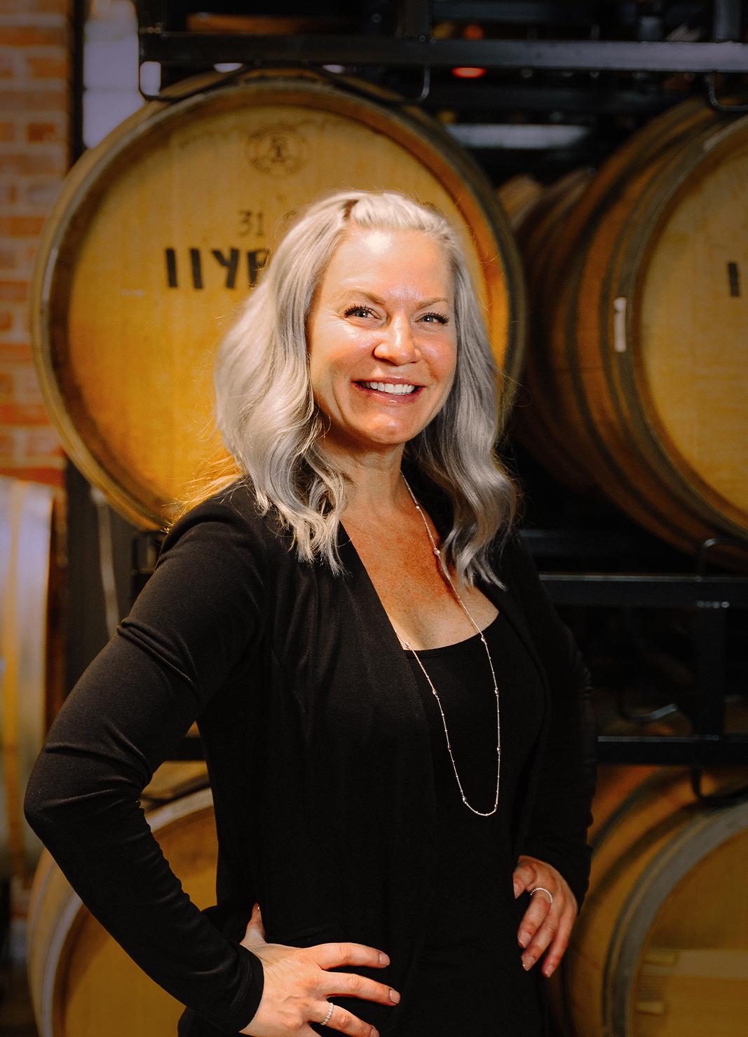 Carboy Tasting Room Manager, Cindy Davis, standing in front of wine barrels