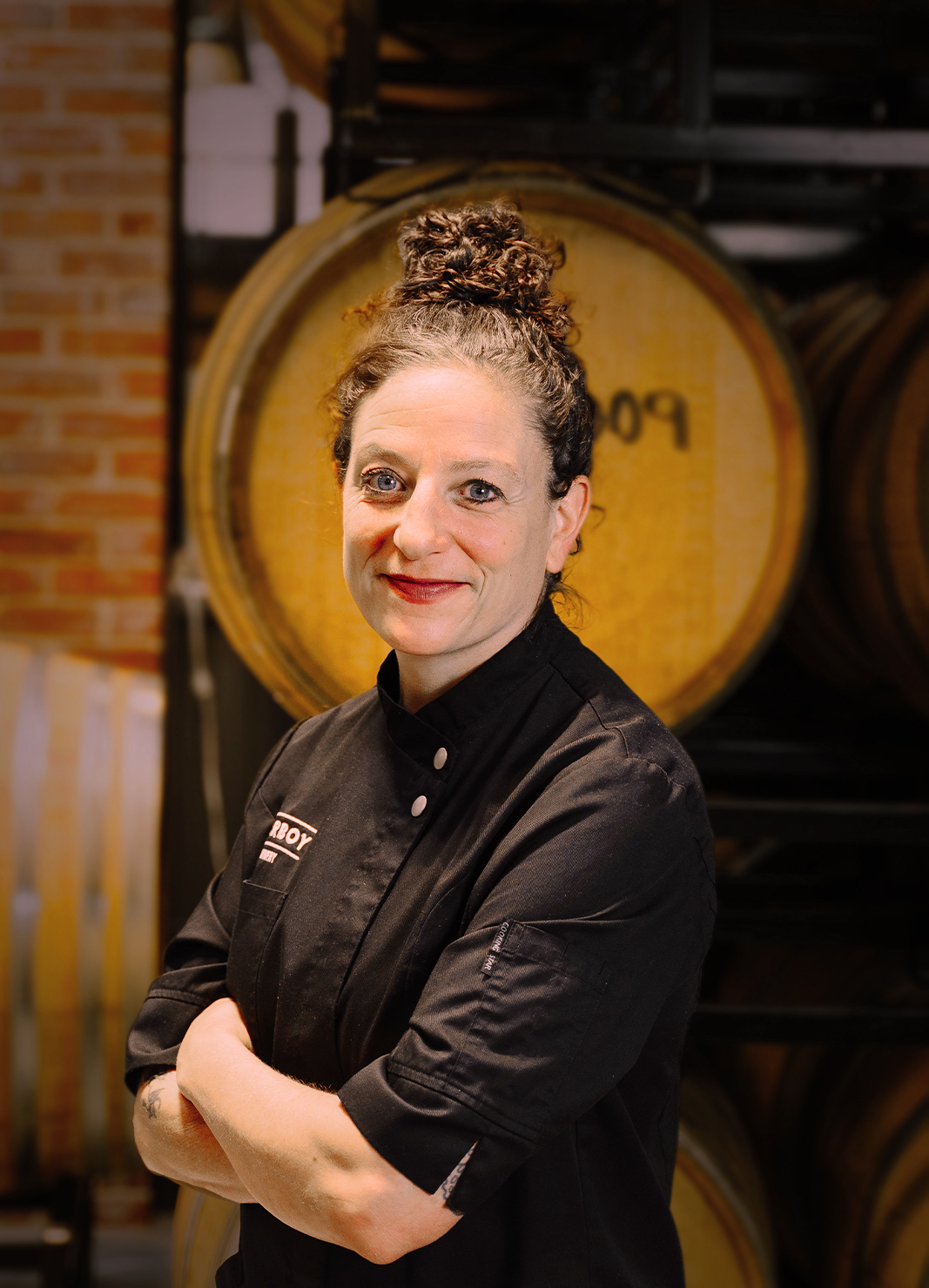 Carboy Executive Chef, Rebecca Weitzman, standing in front of wine barrels