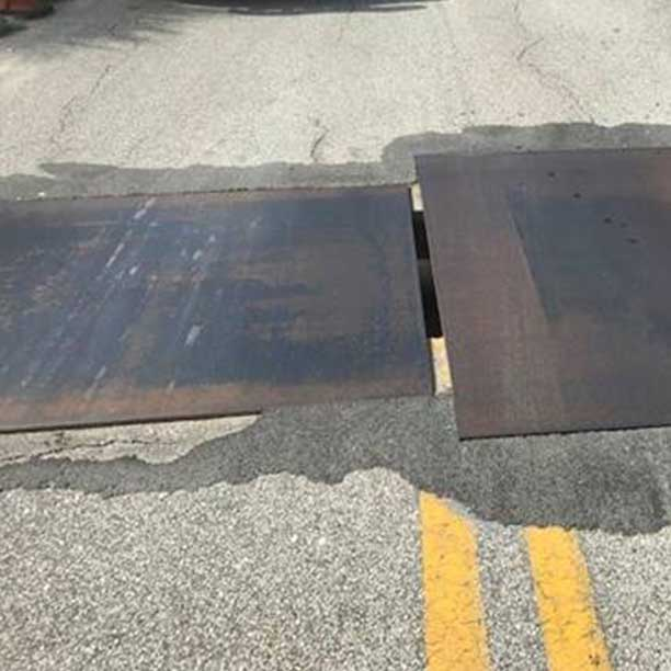 Steel plates covering construction zone holes in road.