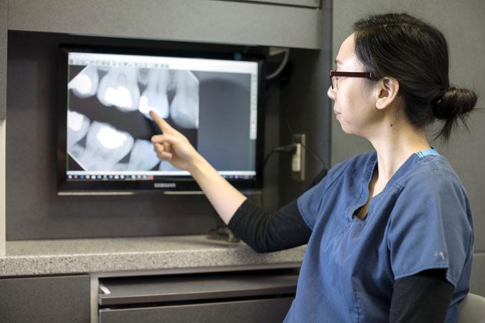 Female dentist explaining x-ray of molars