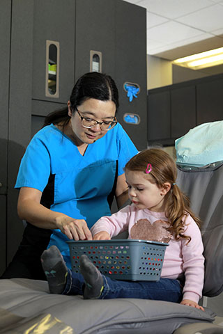Female dentist going through treat basket with female child after an appointment