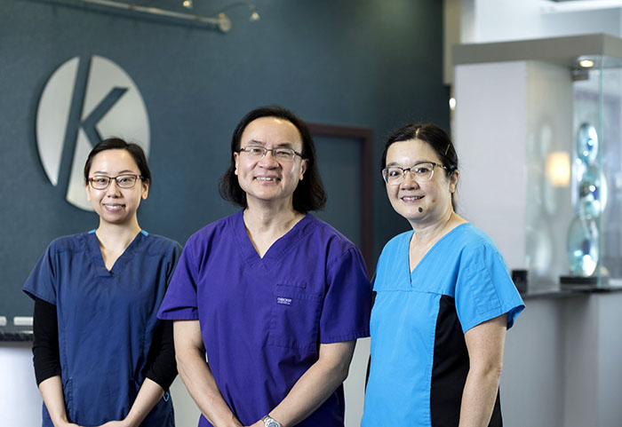 three dentists, two female and one male, posing in front of reception area