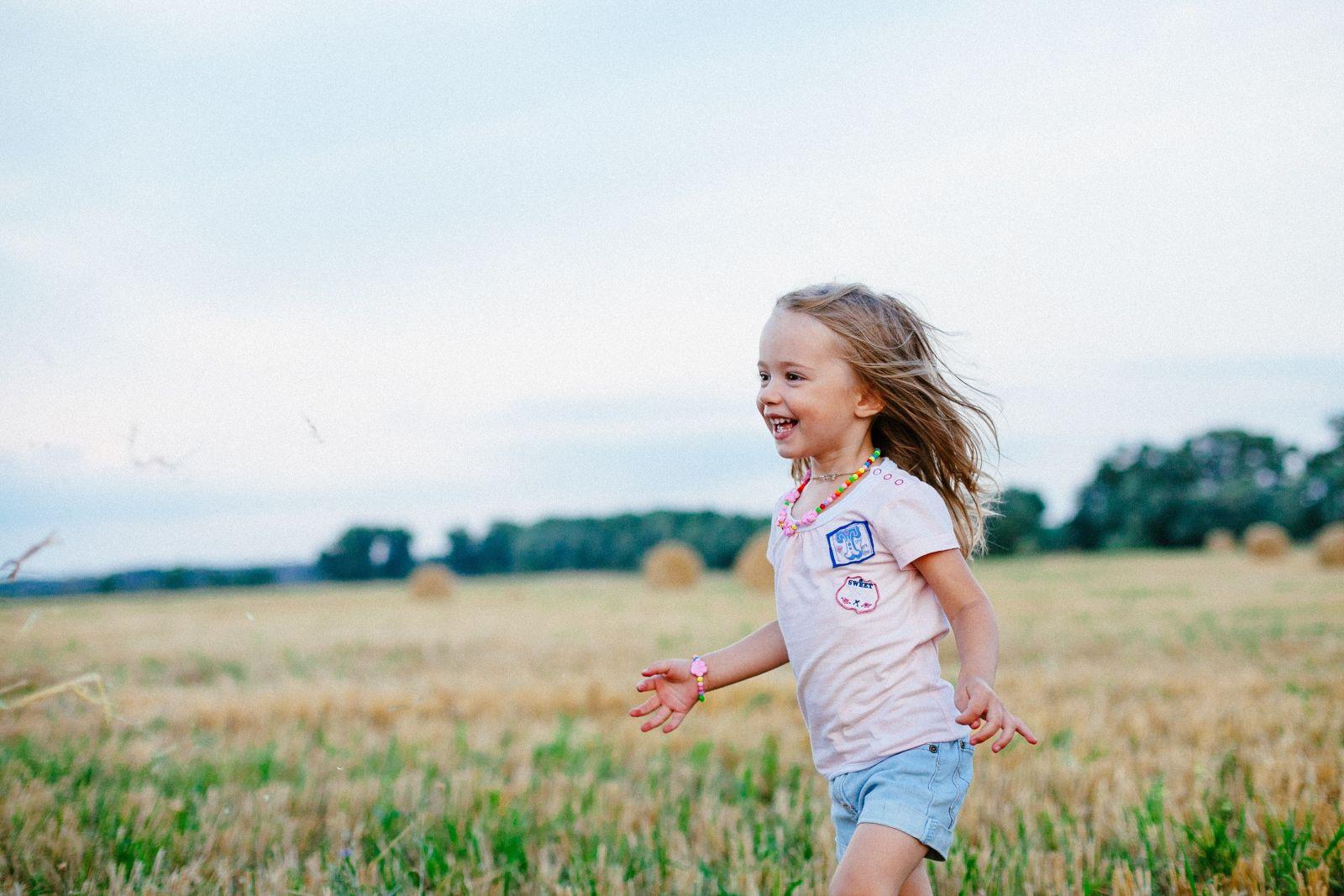Smiling girl running through field