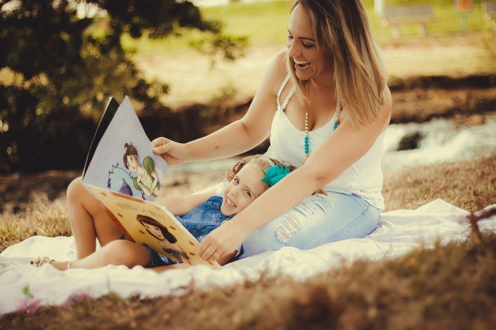 Mom reading book to smiling child
