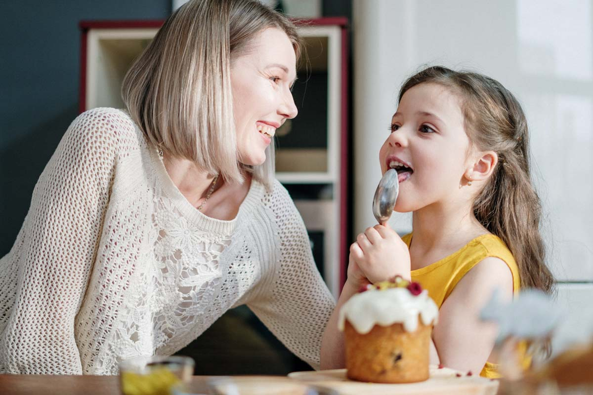 boy happily eating cake with his mother