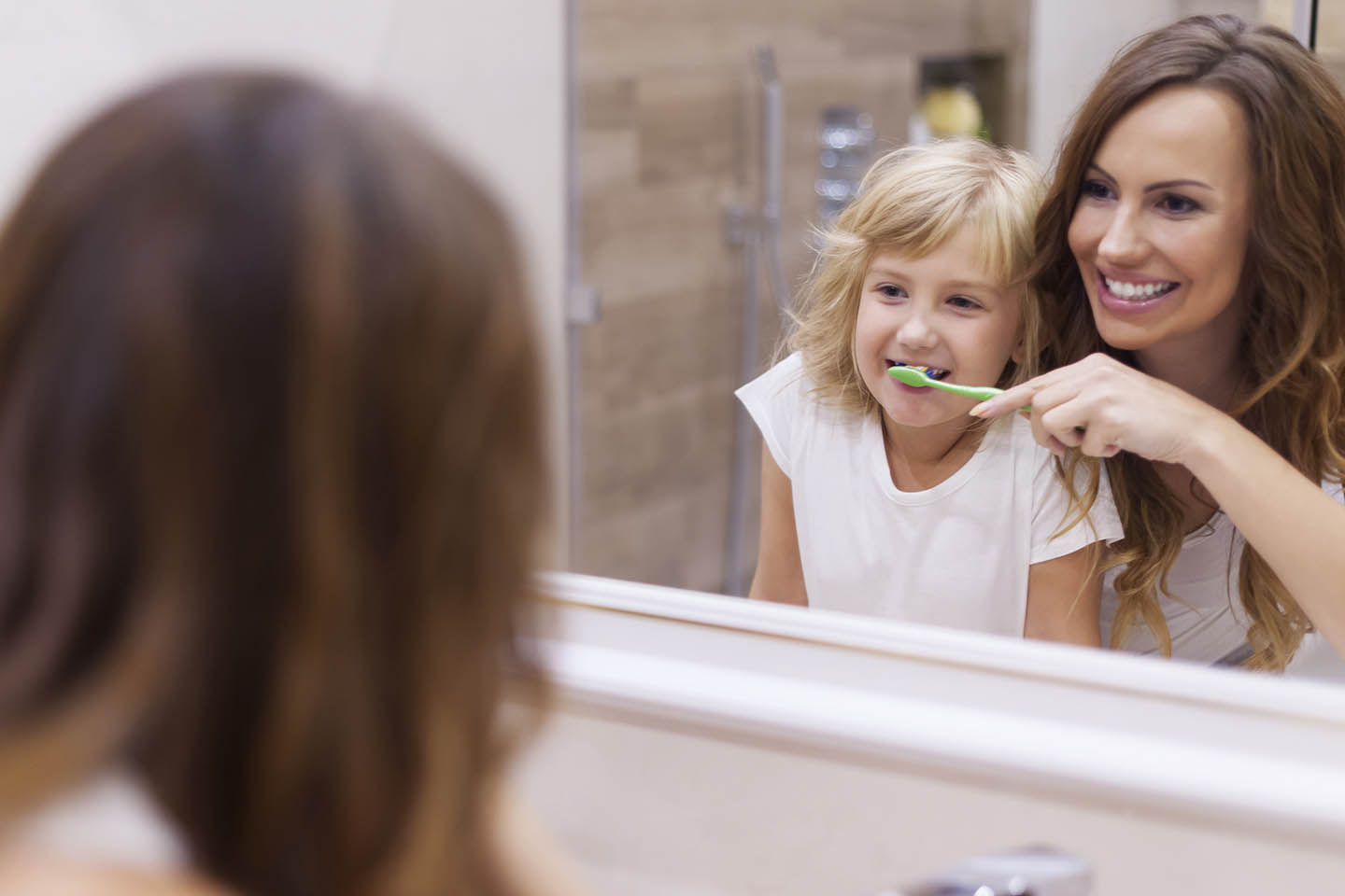 Little girl being helped to brush her teeth