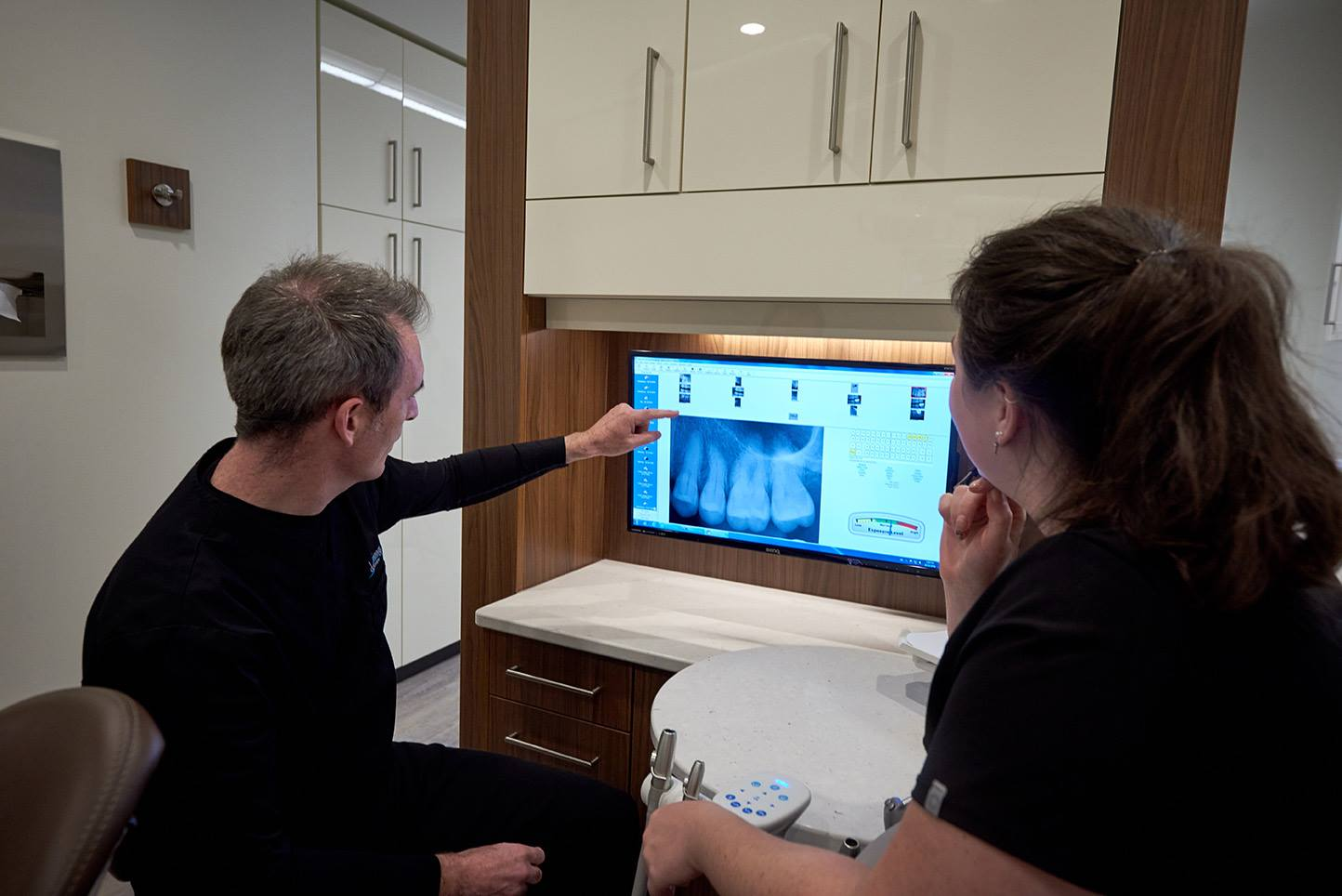 Back of head of a dentist and dental assistant pointing to x-ray of molars.