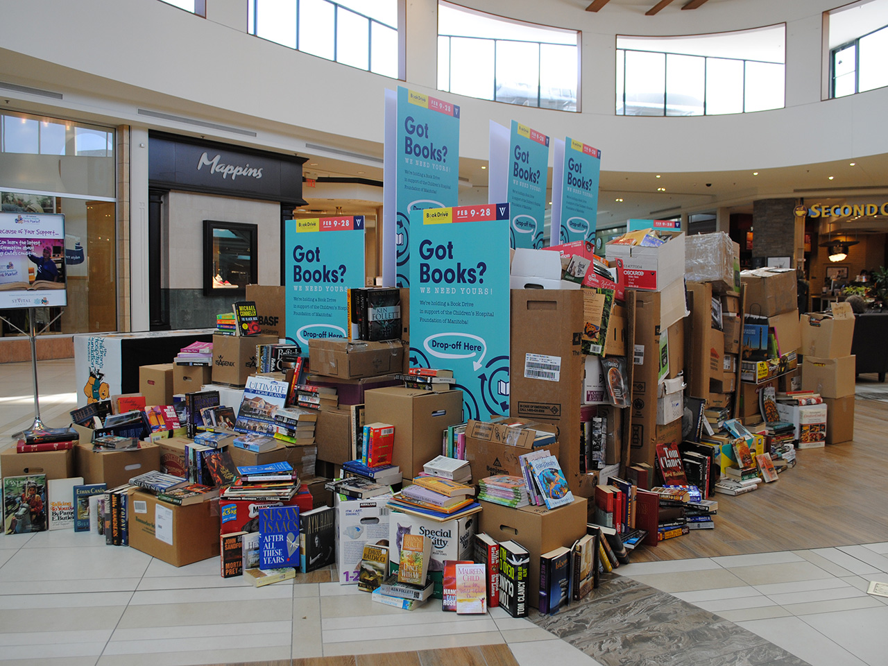 St. Vital Centre's centre court full of books for the book drive. The books are piled high and in many boxes.