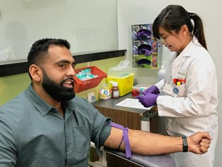 Obby Khan getting his blood test done by a nurse at a Dynacare location