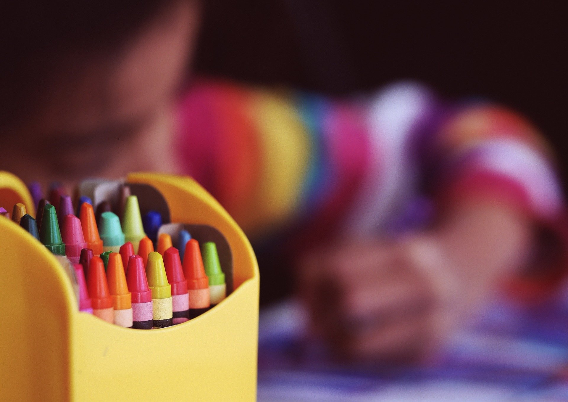 Box of crayons in foreground with child colouring in the background