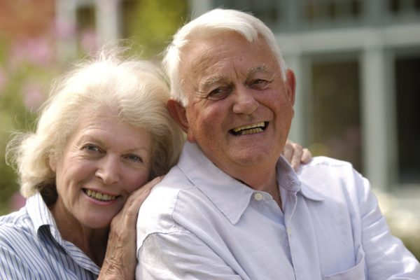 An older couple poses together and shows off their smiles.
