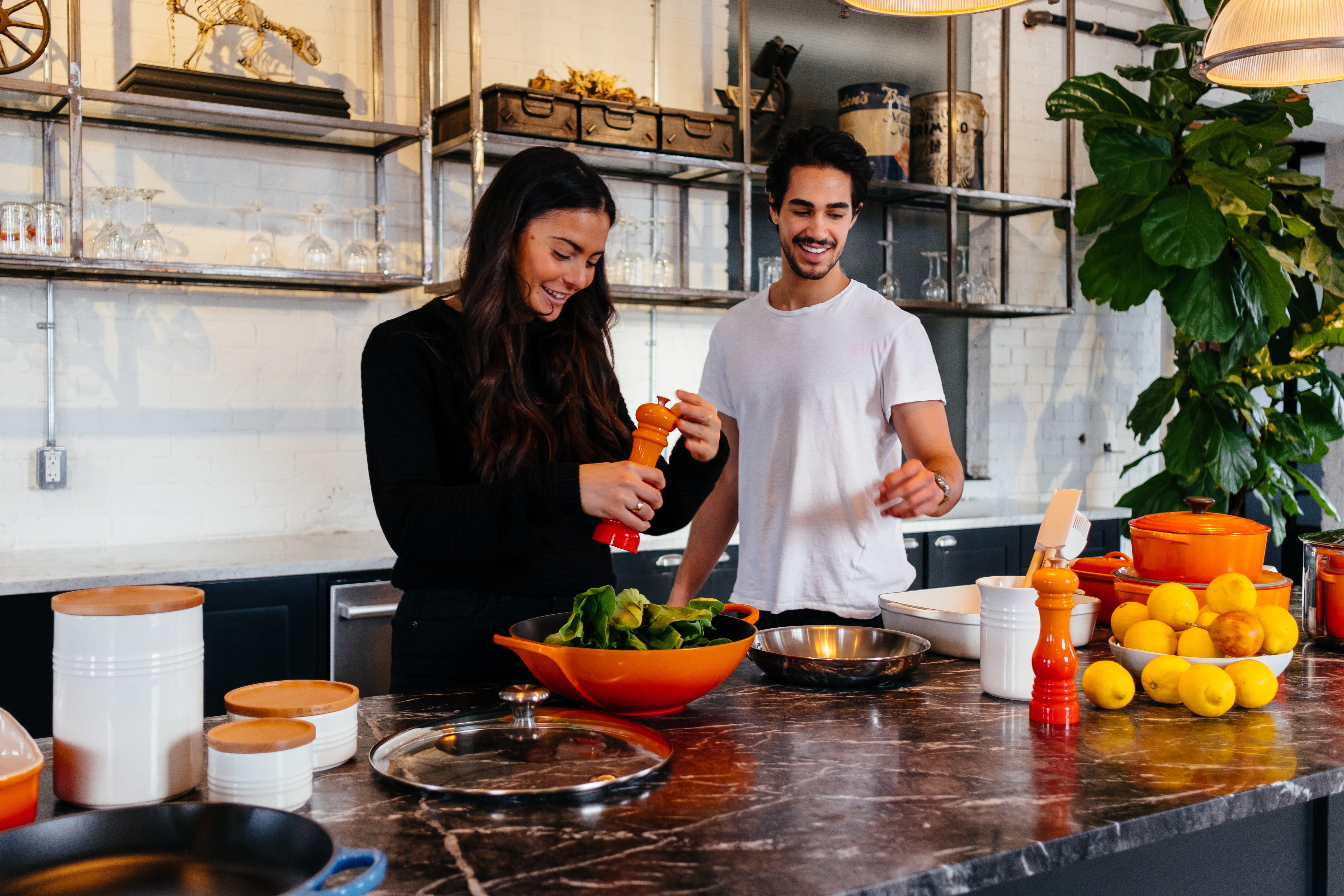 A couple, cooking together, in a kitchen with marble counters, metal shelves in the back and orange bowls, pots and other accents. She's wearing black and has long black hair, he's wearing a white tshirt.