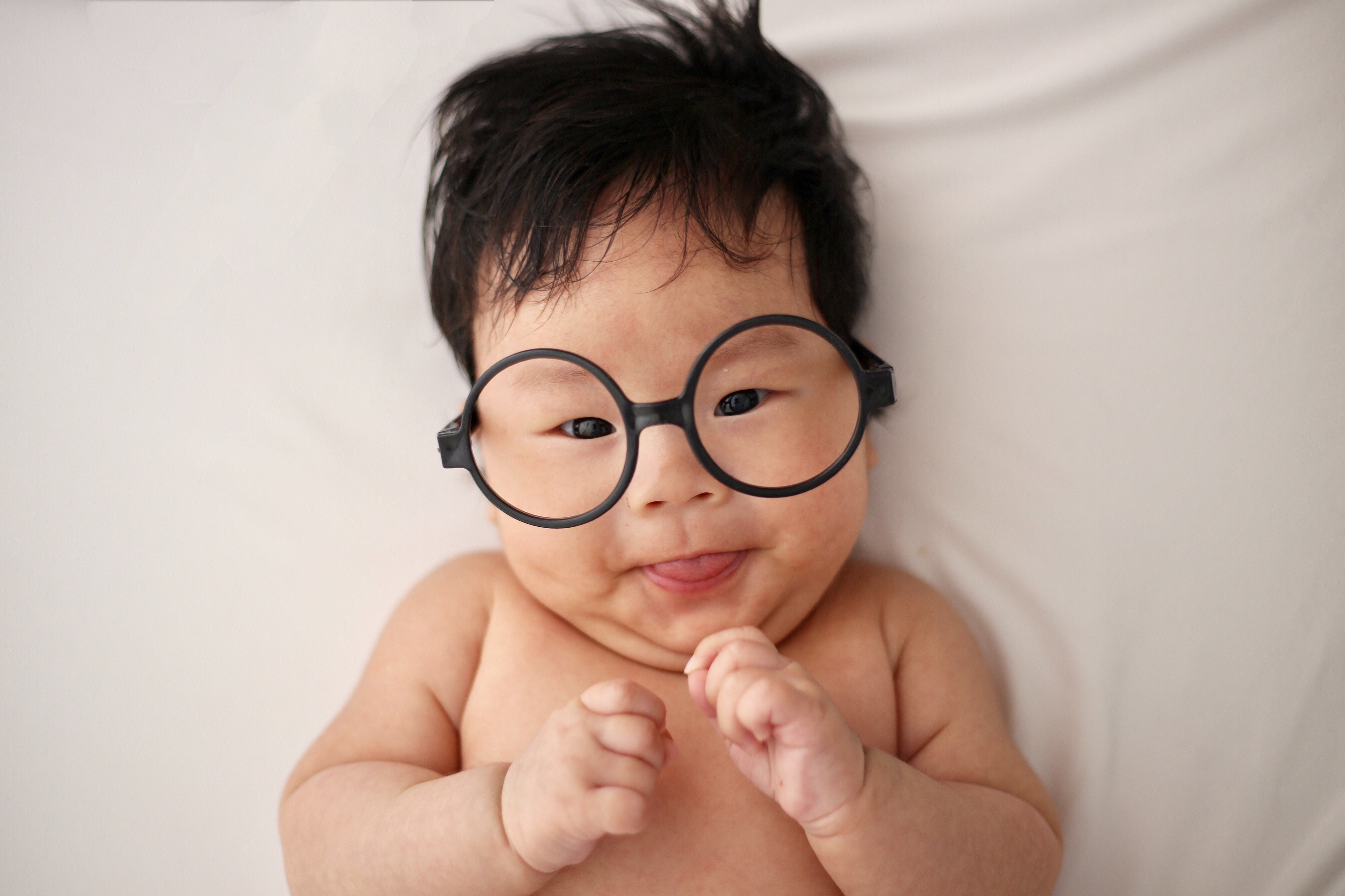 baby in over-sized glasses sticking its tongue out