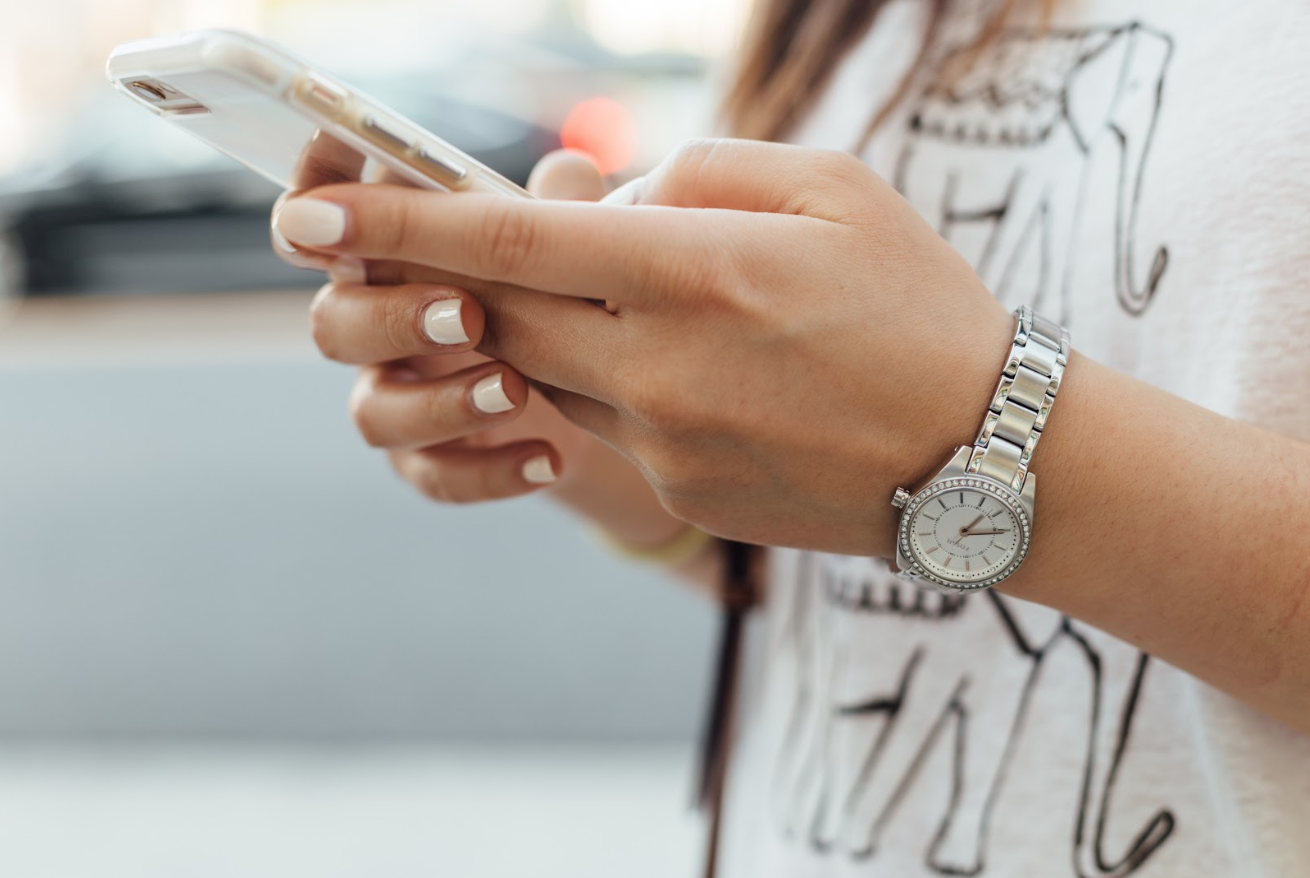 hands, manicured and a watch on, holding a smart phone