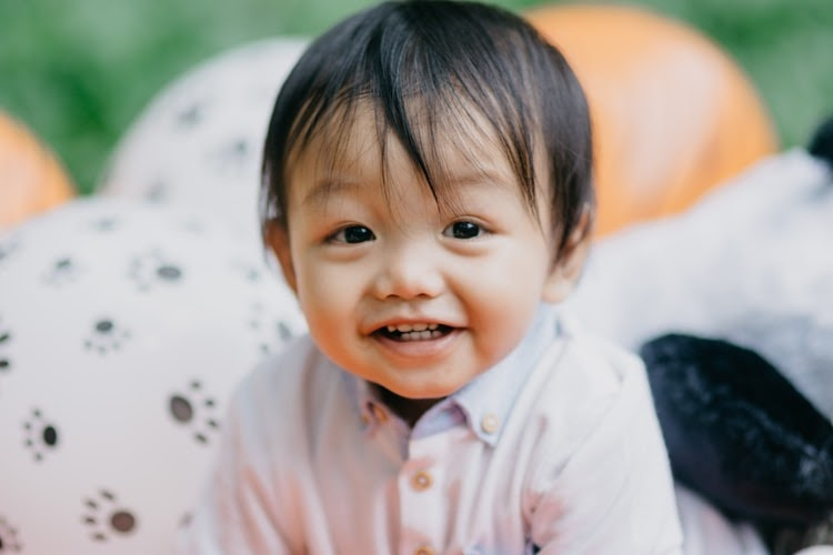 A young baby will full teeth smiling.