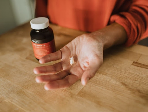 Person holding a probiotic in their left hand.